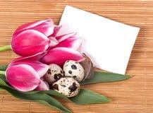 Αυγά Πάσχας με τις ρόδινες τουλίπες ανθοδεσμών Στοκ Εικόνες