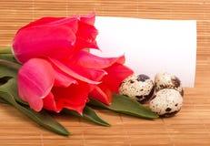 Αυγά Πάσχας με τις ρόδινες τουλίπες ανθοδεσμών Στοκ Φωτογραφίες
