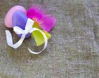 Αυγά Πάσχας με τον κόμβο τόξων και χρωματισμένα φτερά burlap στο υπόβαθρο στοκ φωτογραφία