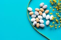 Αυγά Πάσχας με τον κλάδο ανθών στο μπλε πρότυπο άποψης υποβάθρου τοπ Στοκ Φωτογραφία