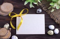 Αυγά Πάσχας με burlap πράσινη κορδέλλα κλάδων υφασμάτων την κίτρινη και διάστημα για το κείμενο Στοκ Φωτογραφίες