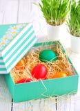 Αυγά Πάσχας που χρωματίζονται με τα οργανικά χρώματα σε ένα κιβώτιο στο σανό Στοκ εικόνα με δικαίωμα ελεύθερης χρήσης