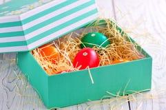 Αυγά Πάσχας που χρωματίζονται με τα οργανικά χρώματα σε ένα κιβώτιο στο σανό Στοκ εικόνες με δικαίωμα ελεύθερης χρήσης