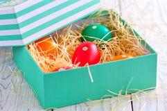 Αυγά Πάσχας που χρωματίζονται με τα οργανικά χρώματα σε ένα κιβώτιο στο σανό Στοκ Εικόνες