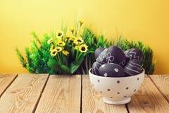 Αυγά Πάσχας που χρωματίζονται με το χρώμα πινάκων κιμωλίας στον ξύλινο πίνακα Στοκ Εικόνα