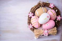 Αυγά Πάσχας που χρωματίζονται στα χρώματα κρητιδογραφιών στη φωλιά Στοκ Φωτογραφία