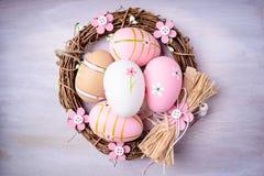 Αυγά Πάσχας που χρωματίζονται στα χρώματα κρητιδογραφιών στη φωλιά Στοκ εικόνα με δικαίωμα ελεύθερης χρήσης