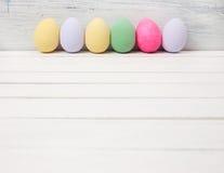 Αυγά Πάσχας που χρωματίζονται στα χρώματα κρητιδογραφιών στο άσπρο ξύλο Στοκ εικόνα με δικαίωμα ελεύθερης χρήσης