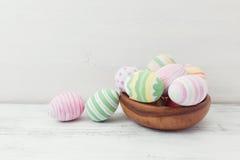 Αυγά Πάσχας που χρωματίζονται στα χρώματα κρητιδογραφιών στο άσπρο ξύλινο υπόβαθρο 2 όλα τα αυγά Πάσχας έννοιας νεοσσών κάδων ανθ Στοκ φωτογραφία με δικαίωμα ελεύθερης χρήσης