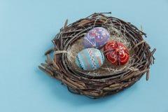 Αυγά Πάσχας που χρωματίζονται στη φωλιά σε ένα μπλε υπόβαθρο Στοκ Εικόνα