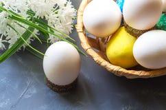 Αυγά Πάσχας σε ένα καλάθι και άσπρα λουλούδια σε ένα σκούρο μπλε υπόβαθρο Στοκ Φωτογραφία