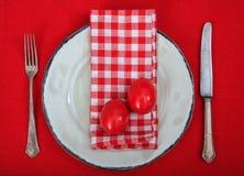 Αυγά Πάσχας σε ένα πιάτο στο κόκκινο τραπεζομάντιλο Στοκ Εικόνες