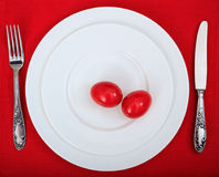 Αυγά Πάσχας σε ένα πιάτο στο κόκκινο τραπεζομάντιλο Στοκ Φωτογραφία