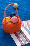 Αυγά Πάσχας σε ένα πορτοκαλί καλάθι στο μπλε υπόβαθρο, Στοκ Εικόνες