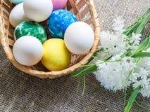 Αυγά Πάσχας σε ένα ψάθινο καλάθι και άσπρα λουλούδια σε ένα υπόβαθρο καμβά Στοκ εικόνες με δικαίωμα ελεύθερης χρήσης