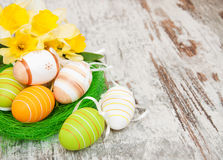 Αυγά Πάσχας σε μια φωλιά με τα λουλούδια στοκ εικόνα με δικαίωμα ελεύθερης χρήσης