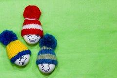 Αυγά Πάσχας σε πράσινο αισθητό Emoticons στο πλεκτό καπέλο με το pom-pom Στοκ Φωτογραφίες