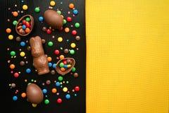 Αυγά Πάσχας σοκολάτας, λαγουδάκι Πάσχας, ζωηρόχρωμες πτώσεις καραμελών, στο α Στοκ Φωτογραφίες