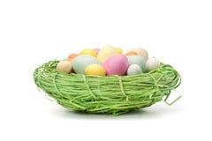 Χρωματισμένα κρητιδογραφία αυγά Πάσχας σε μια μικρή φωλιά Στοκ Εικόνες