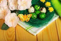 Αυγά Πάσχας στη φωλιά, τα λουλούδια, τις πεταλούδες, την πετσέτα και το ελαφρύ δέντρο Στοκ φωτογραφία με δικαίωμα ελεύθερης χρήσης