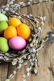 Αυγά Πάσχας στη φωλιά ιτιών, λουλούδια πέρα από το ξύλινο αγροτικό υπόβαθρο Στοκ Φωτογραφίες