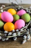 Αυγά Πάσχας στη φωλιά ιτιών, λουλούδια πέρα από το ξύλινο αγροτικό υπόβαθρο Στοκ φωτογραφίες με δικαίωμα ελεύθερης χρήσης