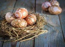 Αυγά Πάσχας στη φωλιά στο αγροτικό ξύλινο υπόβαθρο Στοκ εικόνα με δικαίωμα ελεύθερης χρήσης