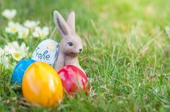 Αυγά Πάσχας στη χλόη και το λαγουδάκι Πάσχας στοκ εικόνες