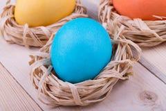 Αυγά Πάσχας στις μικρές φωλιές στο ξύλινο υπόβαθρο Στοκ Εικόνα
