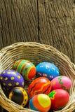 Αυγά Πάσχας στο καλάθι και το ξύλινο υπόβαθρο Στοκ εικόνα με δικαίωμα ελεύθερης χρήσης