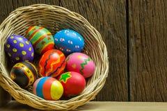 Αυγά Πάσχας στο καλάθι και το ξύλινο υπόβαθρο Στοκ Εικόνες