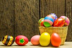 Αυγά Πάσχας στο καλάθι και το ξύλινο υπόβαθρο Στοκ Εικόνα