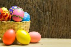 Αυγά Πάσχας στο καλάθι και το ξύλινο υπόβαθρο Στοκ φωτογραφία με δικαίωμα ελεύθερης χρήσης