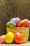 Αυγά Πάσχας στο καλάθι και το ξύλινο υπόβαθρο Στοκ Φωτογραφία