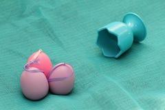 Αυγά Πάσχας στο κυανό υπόβαθρο Πορφυρά διακοσμητικά αυγά Πάσχας στην μπλε σύσταση υποβάθρου Πορφυρό αυγό με το κύπελλο σε κυανό Στοκ Εικόνες