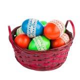 Αυγά Πάσχας στο κόκκινο καλάθι που απομονώνεται πέρα από το άσπρο υπόβαθρο Στοκ φωτογραφία με δικαίωμα ελεύθερης χρήσης