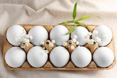 Αυγά Πάσχας στο μεταφορέα χαρτοκιβωτίων που διακοσμείται με τα λουλούδια Στοκ εικόνα με δικαίωμα ελεύθερης χρήσης