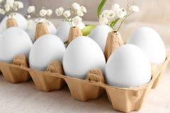 Αυγά Πάσχας στο μεταφορέα χαρτοκιβωτίων που διακοσμείται με τα λουλούδια Στοκ Φωτογραφίες