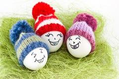 Αυγά Πάσχας στο πράσινο σίζαλ Emoticons στο πλεκτό καπέλο με pom-po Στοκ Φωτογραφίες