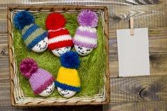 Αυγά Πάσχας στο πράσινο σίζαλ Emoticons στο πλεκτό καπέλο με pom-po Στοκ Φωτογραφία