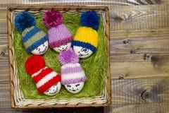 Αυγά Πάσχας στο πράσινο σίζαλ Emoticons στο πλεκτό καπέλο με pom-po Στοκ Εικόνες