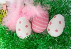 Αυγά Πάσχας, φτερά και λουλούδια στην πράσινη χλόη στοκ εικόνα