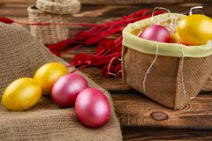 Αυγά Πάσχας sackcloth και ξύλινο ένα υπόβαθρο Ευτυχή φωτεινά πολύχρωμα λαμπρά Πάσχα αυγά Πάσχας Υπόβαθρο με τα αυγά Πάσχας στοκ φωτογραφίες