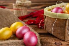 Αυγά Πάσχας sackcloth και ξύλινο ένα υπόβαθρο Ευτυχή φωτεινά πολύχρωμα λαμπρά Πάσχα αυγά Πάσχας Υπόβαθρο με τα αυγά Πάσχας στοκ εικόνες