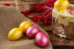 Αυγά Πάσχας sackcloth και ξύλινο ένα υπόβαθρο Ευτυχή φωτεινά πολύχρωμα λαμπρά Πάσχα αυγά Πάσχας Υπόβαθρο με τα αυγά Πάσχας στοκ φωτογραφίες με δικαίωμα ελεύθερης χρήσης