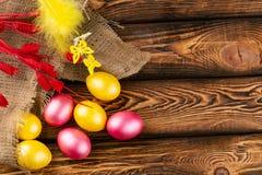 Αυγά Πάσχας sackcloth και ξύλινο ένα υπόβαθρο Ευτυχή φωτεινά πολύχρωμα λαμπρά Πάσχα αυγά Πάσχας Υπόβαθρο με τα αυγά Πάσχας στοκ εικόνες με δικαίωμα ελεύθερης χρήσης
