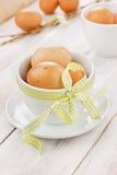 Αυγά Πάσχα με μια κίτρινη κορδέλλα στο άσπρο φλυτζάνι Στοκ εικόνες με δικαίωμα ελεύθερης χρήσης