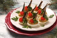 Αυγά που γεμίζονται με τις κλυπέες και το κόκκινο χαβιάρι σε ένα άσπρο πιάτο στοκ φωτογραφίες με δικαίωμα ελεύθερης χρήσης