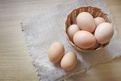 Αυγά σε ένα καλάθι σε ένα ξύλινο επιτραπέζιο υπόβαθρο Στοκ Εικόνες