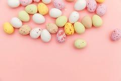 E Αυγά σοκολάτας καραμελών Πάσχας και jellybean γλυκά που απομονώνονται στο καθιερώνον τη μόδα ρόδινο υπόβαθρο κρητιδογραφιών r στοκ φωτογραφία